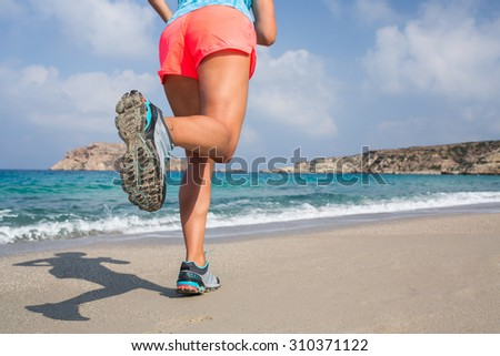 Young woman running on a sandy beach. - stock photo