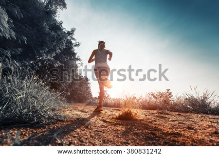 Young woman running on the gravel road at sunset - stock photo