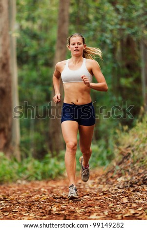 Young Woman Running on Trail - stock photo