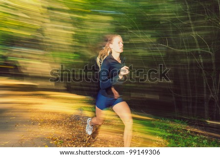 Young Woman Running on Trail with Motion Blur - stock photo