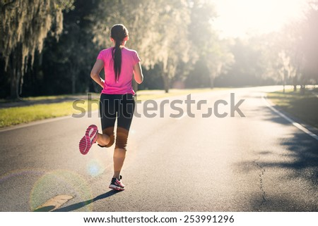 Young woman running outdoors at sunrise or sunset. Wellness and health concept. - stock photo