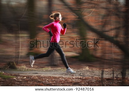 Young woman running outdoors in a city park on a cold fall/winter day (motion blurred image; color toned image) - stock photo