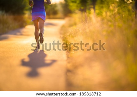 Young woman running outdoors on a lovely sunny summer evening (shallow DOF; color toned image) - stock photo