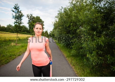 Young woman running outdoors on a lovely sunny winter/fall day - doing the necessary stretching before her run - stock photo