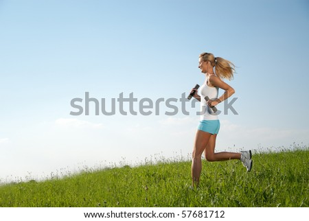 young woman running with dumbbells - stock photo