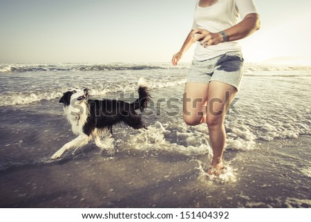 Young woman running with her dog in the shallow water on the beach. - stock photo