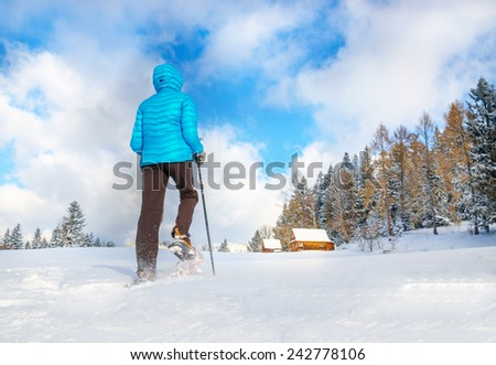 Young woman running with snow shoes in clear snow toward remote cottage house - stock photo