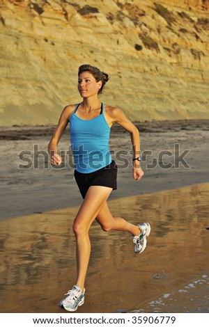 Young woman runs in the surf