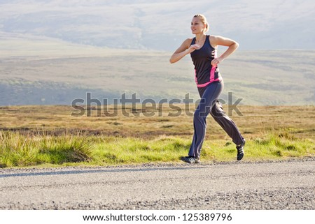 young woman runs outdoor in Wicklow Mountains - stock photo