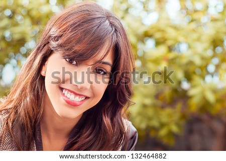 Young woman's closeup portrait smiling out in the park