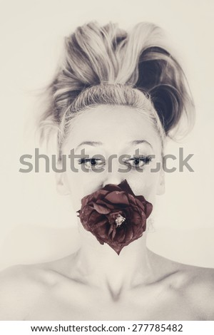Young woman's face with silver makeup, holding a red rose in her mouth - stock photo