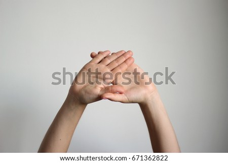 Young woman's fold one's palm isolated on light gray background. Gesture