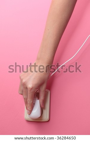 Young woman's hand plugging a power plug into an electric wall socket at a pink wall - stock photo