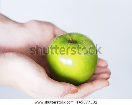 Young woman's hands and green apple