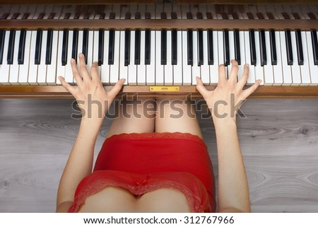 Young woman's hands taking chord on piano  - stock photo