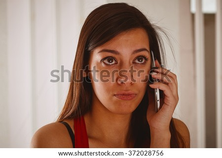 Young woman sadly talking on the phone.  - stock photo