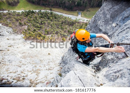 Young woman scaling a rock face - stock photo