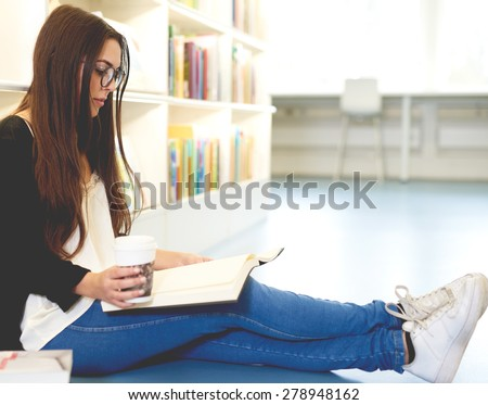 Young woman scholar relaxing with her books sitting stretched out on the floor in the university library doing research while enjoying takeaway coffee - stock photo