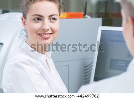 Young woman scientist smiling sitting beside computer