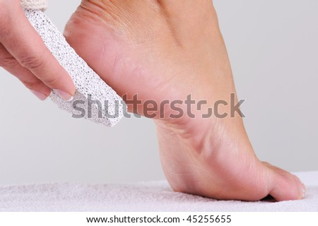 young woman scrubbing her foot by pumice in a beauty salon