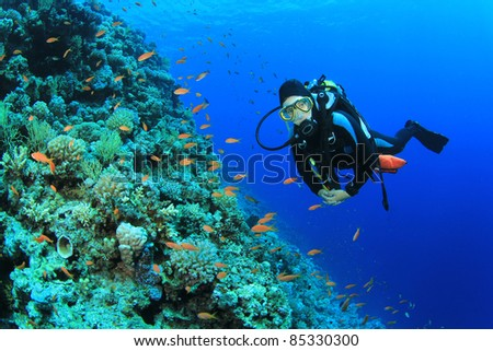 Young Woman Scuba Diver explores a Coral Reef in the Red Sea - stock photo