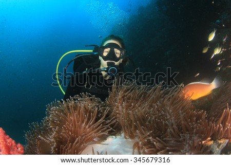Young Woman Scuba diver finds Nemo: Anemonefish clownfish on underwater coral reef - stock photo