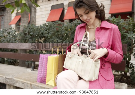 Young woman searching through her handbag while sitting down with shopping bags. - stock photo