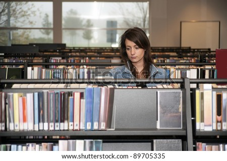 Young woman searching through the books in several bookshelves in a public library - stock photo