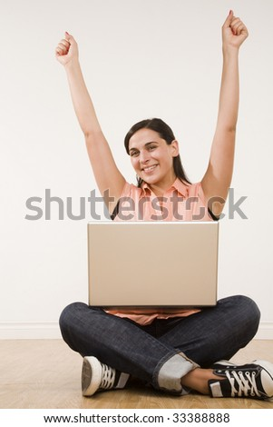 young woman seated on floor with laptop and arms raised with excitment