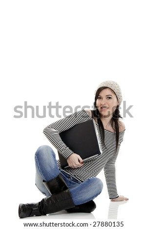 Young woman seated on the floor holding a laptop - stock photo