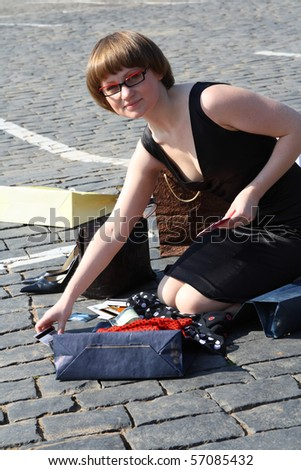 young woman seating near multicolor shopping bags and holding plastic cards in her hand