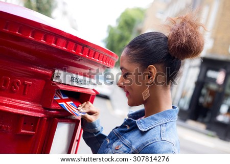 young woman sending a postcard in England