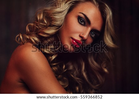 Young woman sensual fashion portrait with makeup and long blond hair in dark interior
