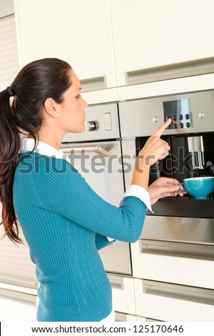 Young woman setting coffee maker machine kitchen cup