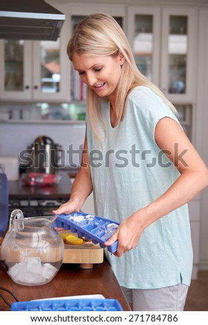 Young woman shaking the ice tray to fill jug in kitchen at home - stock photo