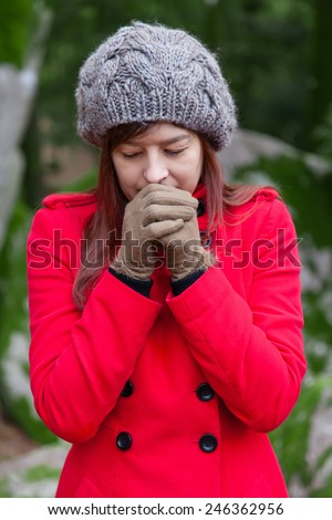 Young woman shivering with cold and blowing hot air to the hands on a forest wearing a red overcoat, a beanie and gloves during winter  - stock photo