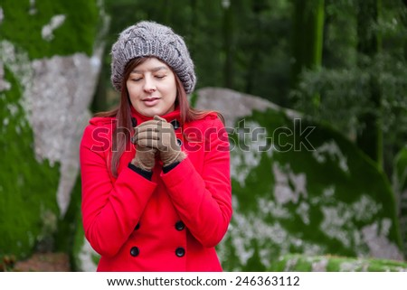 Young woman shivering with cold on a forest wearing a red overcoat, a beanie and gloves during winter  - stock photo
