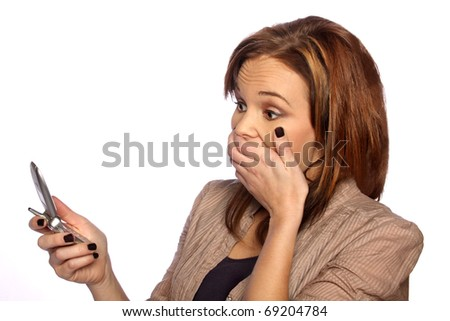 young woman shocked at something on her phone - stock photo