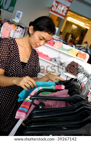 Young woman shopping at a fashion store during sale season - stock photo