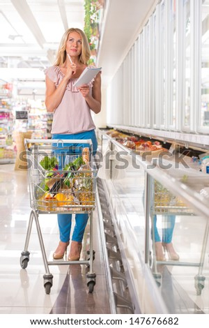 Young woman shopping at supermarket. Holding shopping list and thinking what she should buy next - stock photo