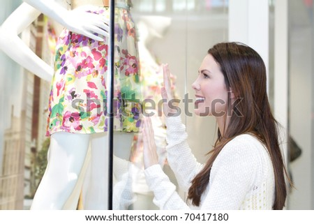 Young woman shopping at the mall for a dress, looking at a store window