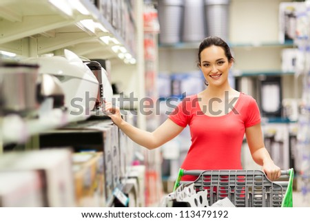 young woman shopping for appliance in supermarket