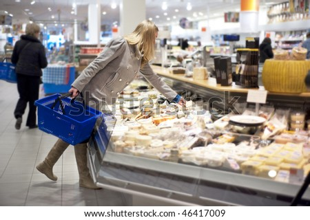 young woman shopping for groceries, and picking a piece of cheese from a display counter in a supermarket. Shallow depth of field