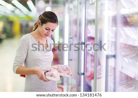 Young woman shopping for meat in a grocery store (color toned image)