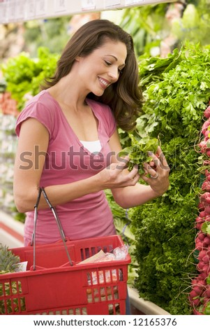 Young woman shopping for produce in supermarket - stock photo