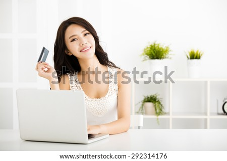Young woman  shopping online with credit card and laptop - stock photo