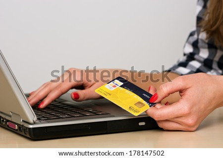 Young woman shopping online with laptop and credit card - stock photo