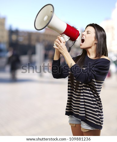 young woman shouting with a megaphone against a street background - stock photo