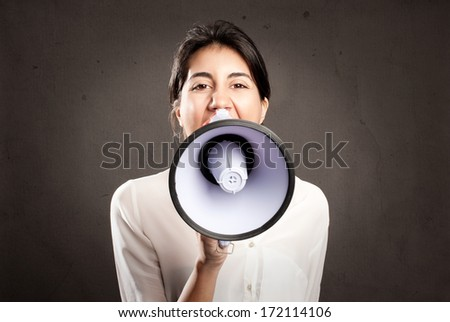 young woman shouting with a megaphone on a gray background