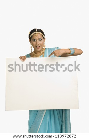 Young woman showing a blank placard and smiling - stock photo